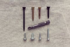Screws and bits for the screwdriver laid out on cotton fabric royalty free stock photography