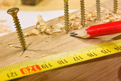 Screws bolted to plank and tape measure with r Royalty Free Stock Photo