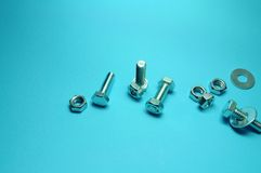 Screws and bolts. In a blue background Royalty Free Stock Photo