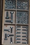 Screws and bolts in a box. Screws and bolts in a wooden box Royalty Free Stock Photo