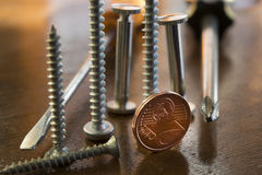 Screws bolts and two cent  to symbolize professions and profits Royalty Free Stock Images