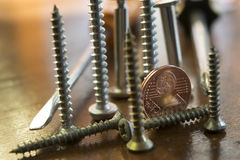 Screws bolts and two cent to symbolize professions and profits. Screws bolts and two cent to symbolize the concept of manual work , professions and monetary stock images