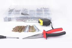 Screws in the box with screwdriver and pliers in the white. Screws in the box with screwdriver and pliers in the white Royalty Free Stock Photo