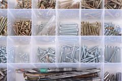 Screws in the box with screwdriver and pliers in the white. Screws in the box with screwdriver and pliers in the white Stock Photography