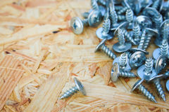 Screws closeup on wooden background Stock Photos