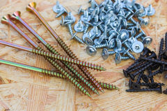 Screws of different sizes on wooden background Royalty Free Stock Photography