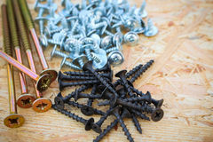 Screws of different sizes on wooden background Royalty Free Stock Images