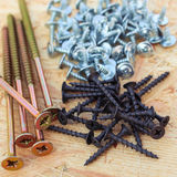 Screws of different sizes on wooden background Stock Photo