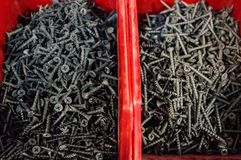 Screws, dowels and nails in red boxes in the mini market for sale. Selective focus. stock images