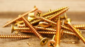 Screws. Golden screws lie on a wooden table Royalty Free Stock Photos