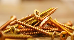 Screws. Golden screws lie on a wooden table Stock Image