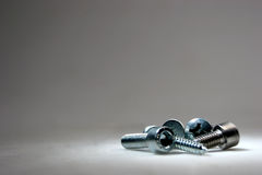 Screws on a grey background. Under a spotlight Royalty Free Stock Image