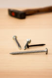Screws and hammer on a table Stock Images