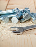 Screws and key on wooden surface Royalty Free Stock Image