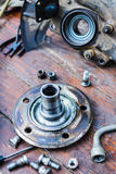 Screws for mounting the wheel hub lie on a wooden table Stock Image