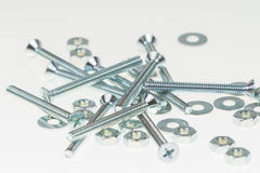 Screws, nuts, and bolts on isolated white background Stock Photos