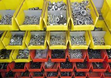 Screws and nuts. Full frame industrial background showing yellow and red boxes filled with lots of various screws and nuts Stock Images