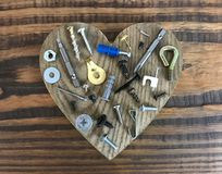 Screws and Nuts on Heart Wood Background. Photo image stock image