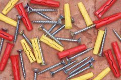 Screws plasctic dowels on brick background. Screws plasctic dowels on red brick background close-up Stock Photo
