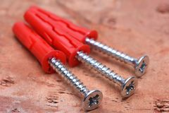 Screws plasctic dowels on brick background. Screws plasctic dowels on red brick background close-up Stock Photography