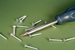 Screws and Screwdriver. Phillips screwdriver and screws on a green background Stock Images