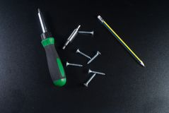 Screws, screwdriver and pencil Stock Photography