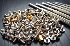 Screws and screwdrivers. Bunch of small screws and precision screwdrivers royalty free stock images