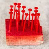 Screws are screwed in wood painted with red paint.  royalty free stock images
