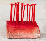 Screws are screwed in wood painted with red paint.  stock photos
