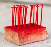 Screws are screwed in wood painted with red paint.  royalty free stock image