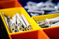 Screws segregated in plastic colored containers. Box for builder. And DIY. Black background Stock Image