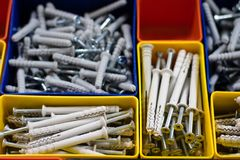 Screws segregated in plastic colored containers. Box for builder. And DIY. Black background Royalty Free Stock Photo
