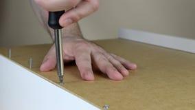 Screws Set in a Row. Close-up of screwing a few screws set in a row with screwdriver stock footage