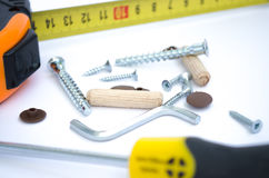 Screws, tape measure and a screwdriver Royalty Free Stock Images