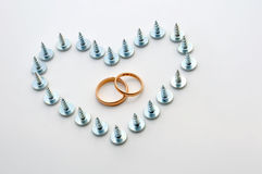 Screws and wedding rings Royalty Free Stock Photos
