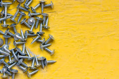 Screws and yellow background. Stock Images
