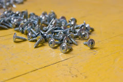 Screws on a yellow table. Stock Photos