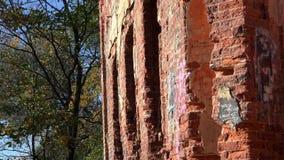 Scribacchiato in pareti del gesso tempi imperiali abbandonati di vecchi di un castello marcio rosso mattone invasi con erba verde video d archivio