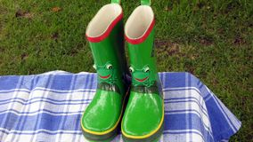 Scribble Childrens Frog Wellington Boots on a Table Royalty Free Stock Photography