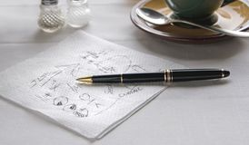 Scribble on Napkin at Table with Pen. Scribble on a Napkin at a Restaurant Table with Pen royalty free stock images