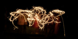 Scribble written with sparklers against a black background Royalty Free Stock Image