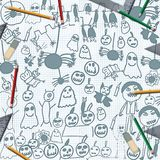 Scribbles of halloween monsters on desk with pencils Royalty Free Stock Images