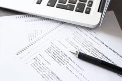 Script il codice su carta, sulla penna e sul computer portatile Fotografia Stock