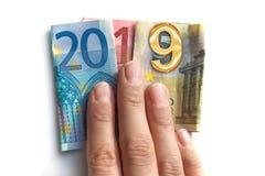 2019 scritto con le banconote degli euro in una mano isolata su bianco immagine stock