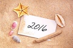 2016, scritto su una nota nella sabbia Fotografie Stock