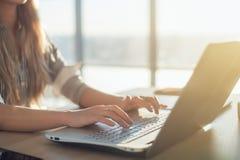 Scrittore femminile che scrive facendo uso della tastiera del computer portatile nel suo luogo di lavoro di mattina Blog online,  Fotografie Stock
