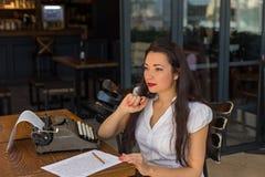 Scrittore femminile con la macchina da scrivere d'annata che fa le note in un caffè s fotografia stock