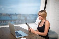 Scrittore femminile di stile di vita che chiacchiera sulla compressa digitale Immagine Stock
