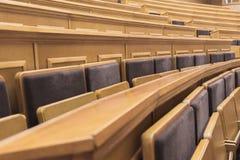 Scrittori di legno con le sedie nel corridoio di conferenza Immagini Stock