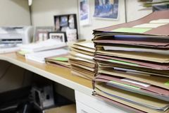 Scrittorio accatastato su con gli archivi ed il lavoro fotografia stock